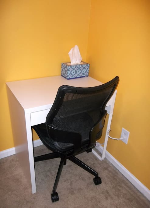 A small desk with a power strip