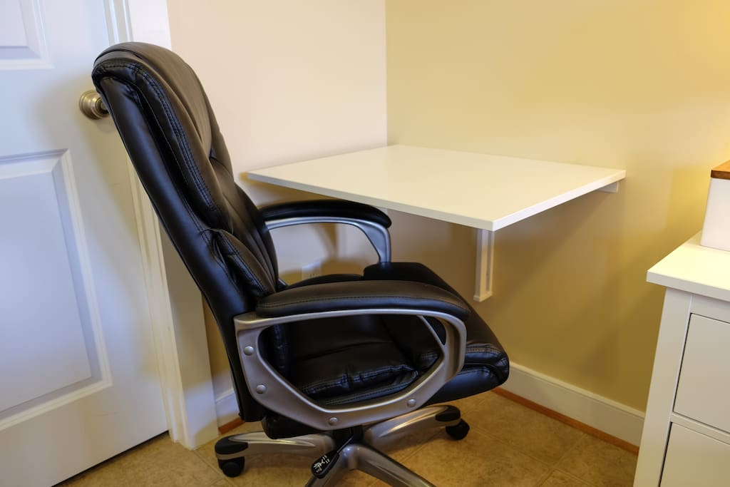 Wall-Mounted Drop-Leaf Desk with Padded Black Leather Chair and Easy Access to Outlets