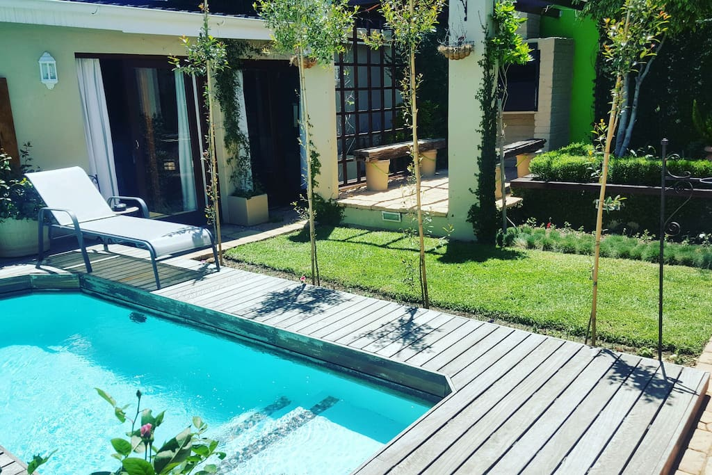 Pool deck with loungers surrounded by the tranquil and secluded garden.