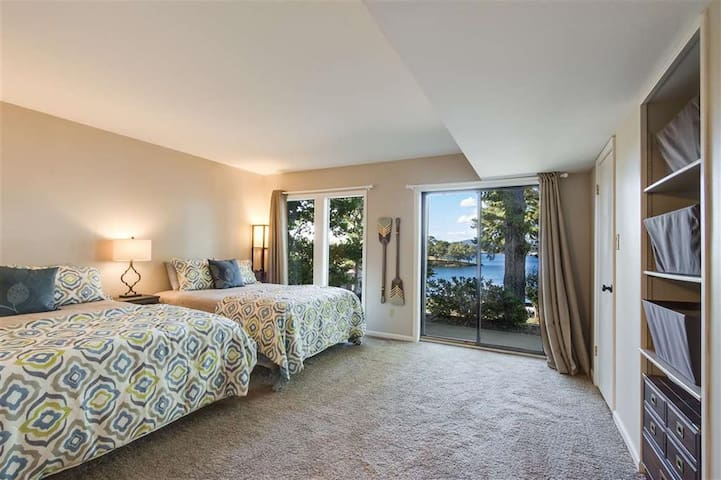 Downstairs bedroom with 2 queen beds and sliding glass doors opening to bottom balcony