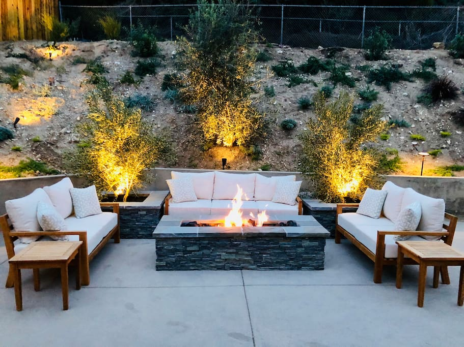 Patio seating with fire table near the pool.