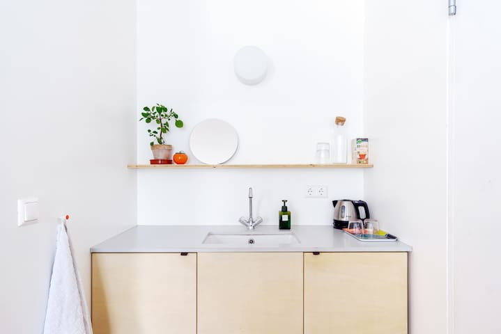 Sink with water cooker. In the cupboard you'll find a few pieces of cutlery, plates, hairdryer, tissues and soap