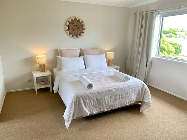 Your very spacious master bedroom with an en-suite bathroom and walk-in robe. Featuring a queen-size bed with pristine linen and plush pillows. Your personal sanctuary after a day at the beach!