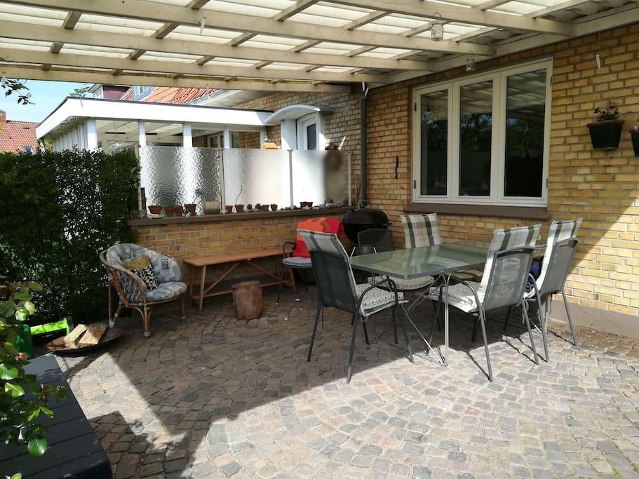 Stor rummelig overdækket terrasse som bruges som ekstra rum.