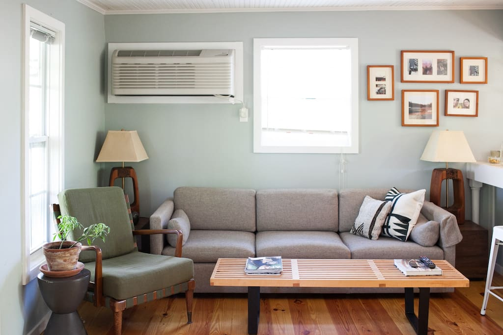 Cozy living room, open to kitchen and bedroom, lets in plenty of natural light.