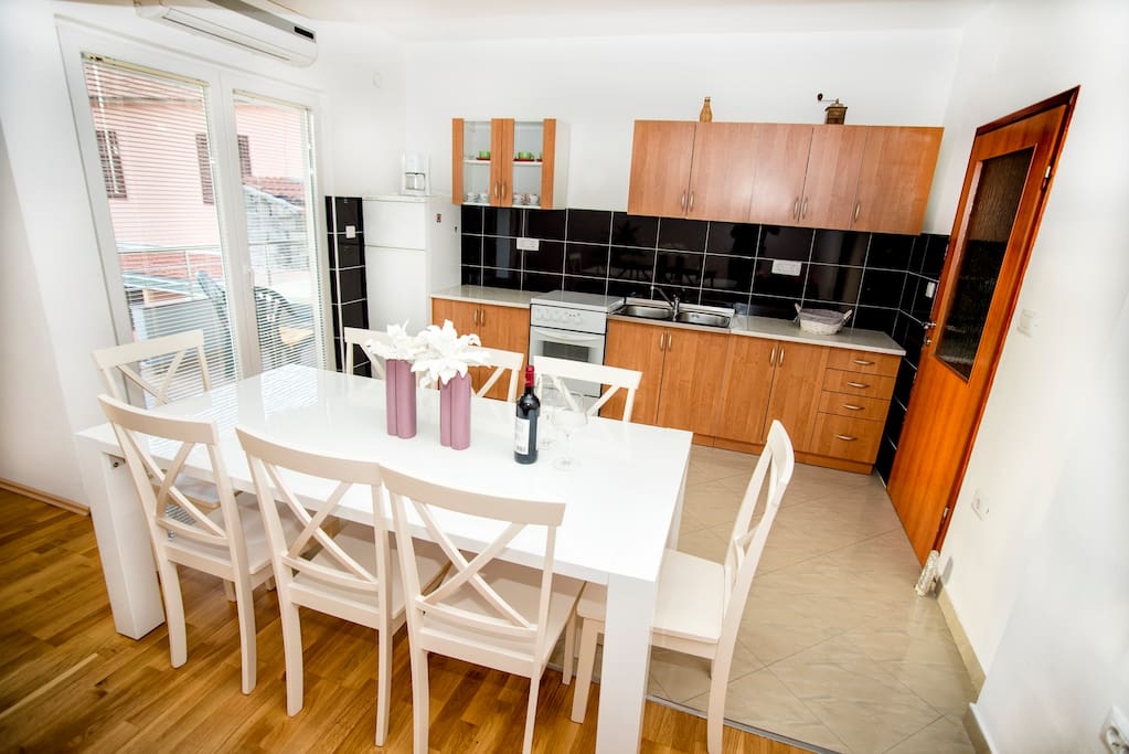 Dinning table, kitchen and entrance to balcony.