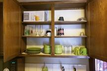 Kitchen cabinet with plates, bowls, mugs, and glasses.