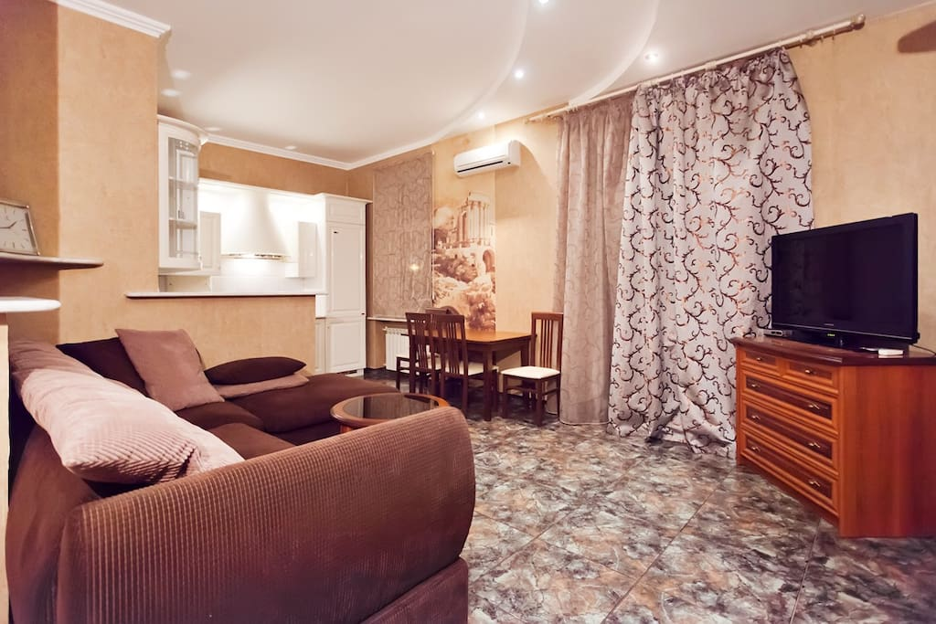 A living room with kitchen area - studio. large corner sofa-bed, air conditioning, large screen TV, a dinner table and 4 chairs. The kitchen is fully equipped with all the dishes.