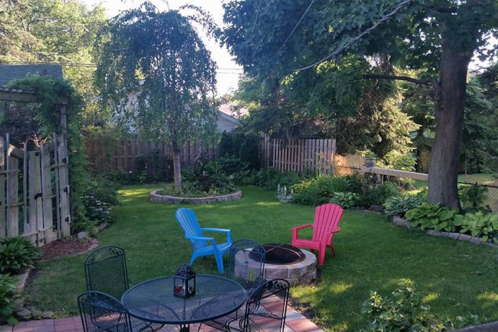 Beautifully landscaped back yard with perennial gardens and fire pit