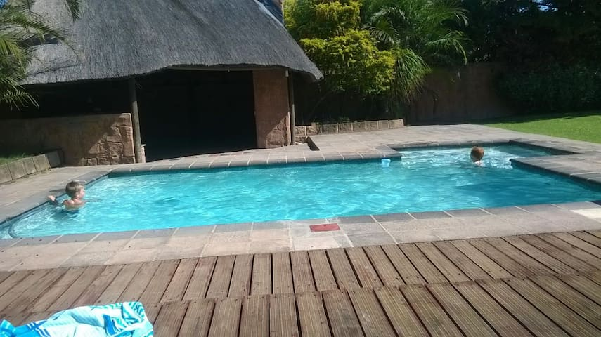 Swimming pool with Thatched lapa, built in braai & bar area with pool table, bar fridge & lights