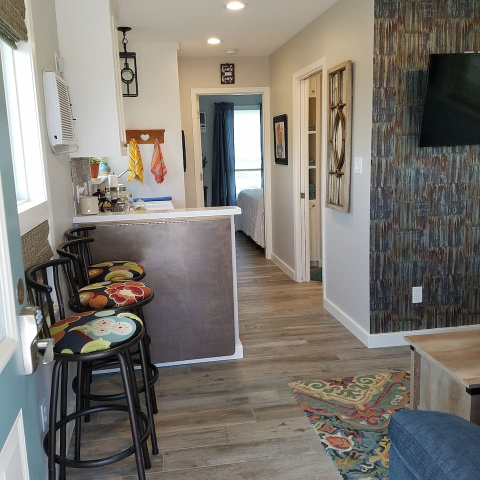 From front door to back wall: full of delightful surprises! Full kitchen. Full bath with floor-to-ceiling tile. Drop leaf table to eat, work or ponder all while enjoying the views from the many windows.
