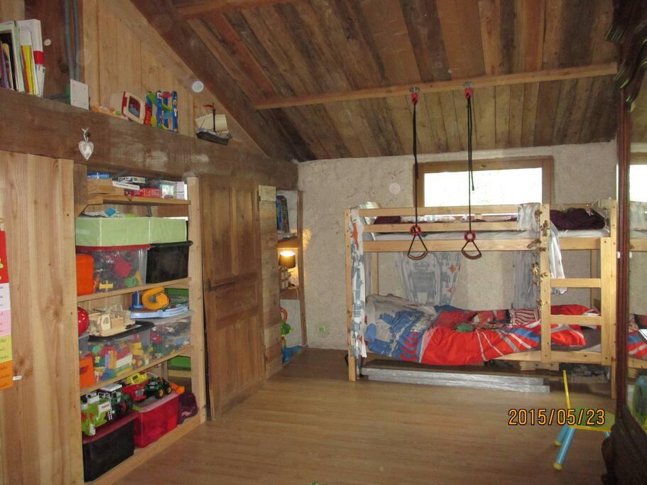 grande chambre avec un lit superposé et un lit à barreau