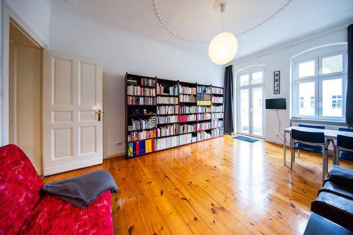 Wohnzimmer mit Schlafcouch für zwei Personen. Im Hintergrund unsere Bibliothek mit über 1.000 Büchern.