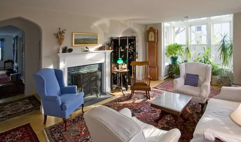 Living area is welcoming and bright, with an upholstered window seat in the bay window.