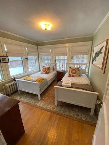 This bedroom offers two twin beds, air conditioning, and 6 windows for a wonderful breeze.