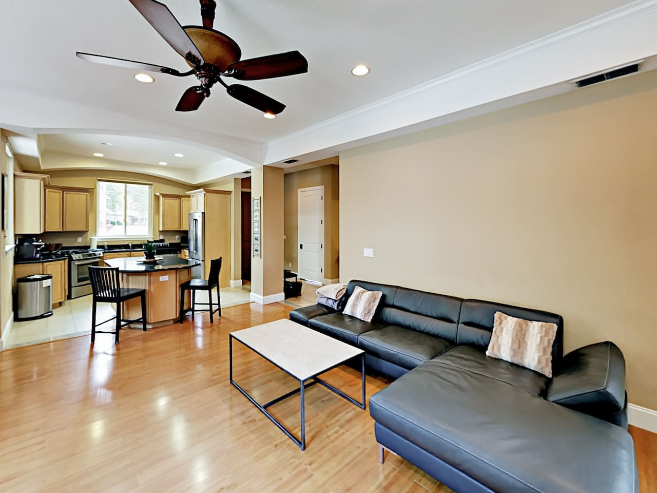 The sunlit living room has seating for 7.