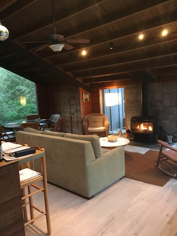 Open concept common area with living room, gas fireplace, kitchen, counter stools and 6 person dining area