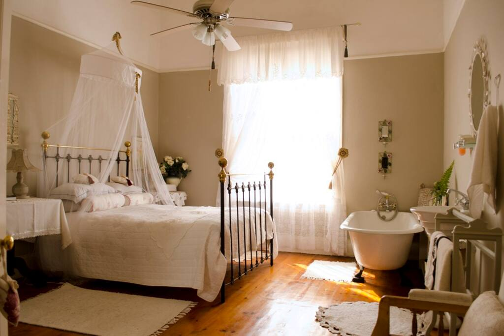 A classic style room with double bed, and a vintage bath tub in the room.