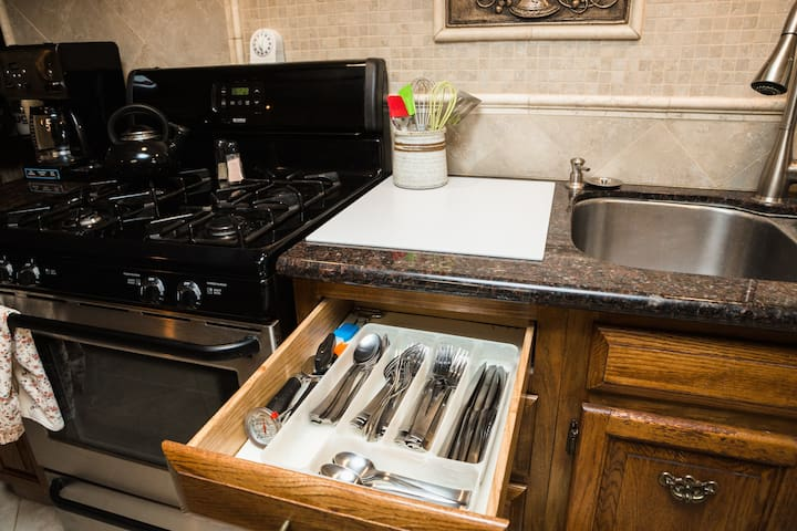 Fully stocked kitchen with pots and pans, cooking utensils,  silverware and dishes.