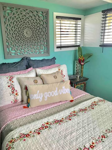 Smaller bedroom with full bed, dressing table and small closet.