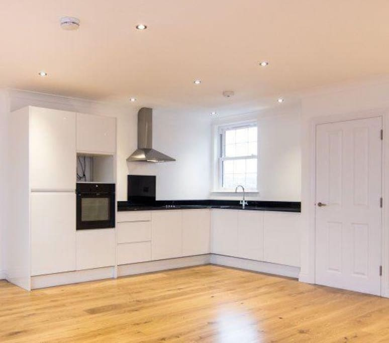 Clean, modern kitchen with built in appliances (including dish washer and washing machine)