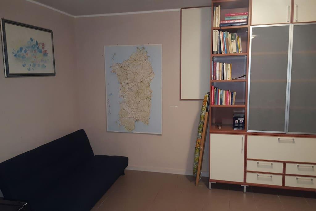 Soggiorno con divano x 1 e cartina della Sardegna per organizzare le escursioni.