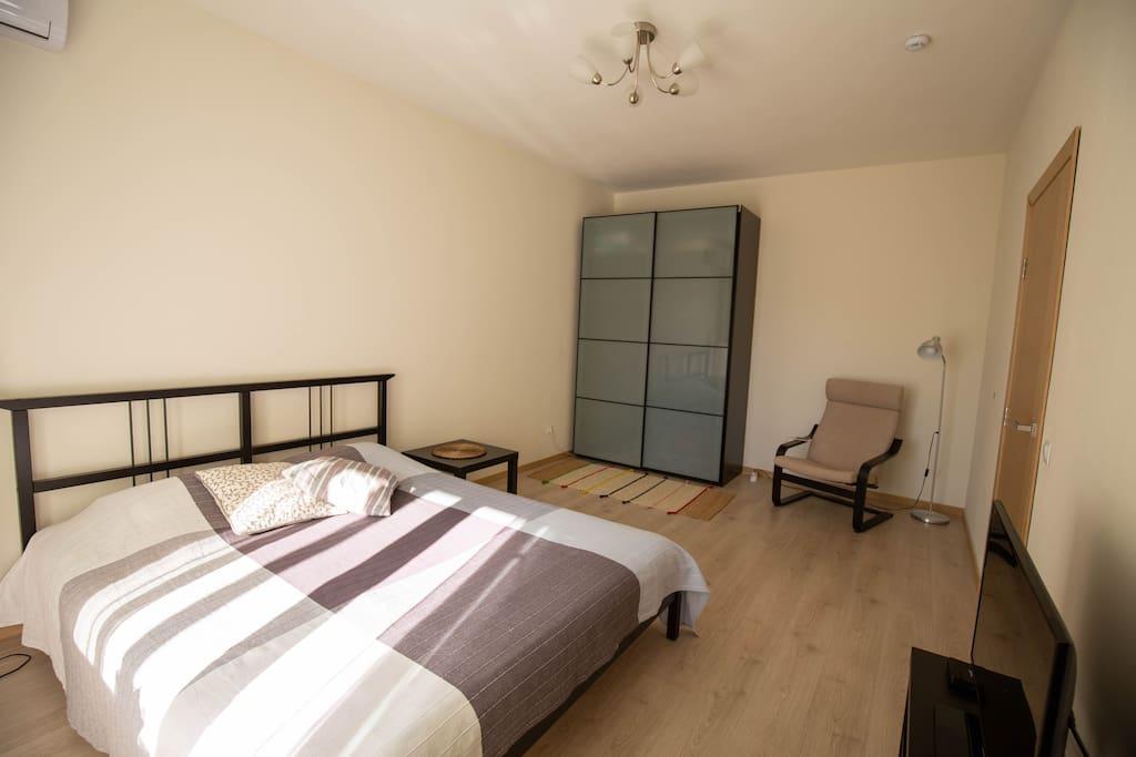 В противоположной стороне от кровати располагается шкаф-купе и удобное кресло с лампой для чтения