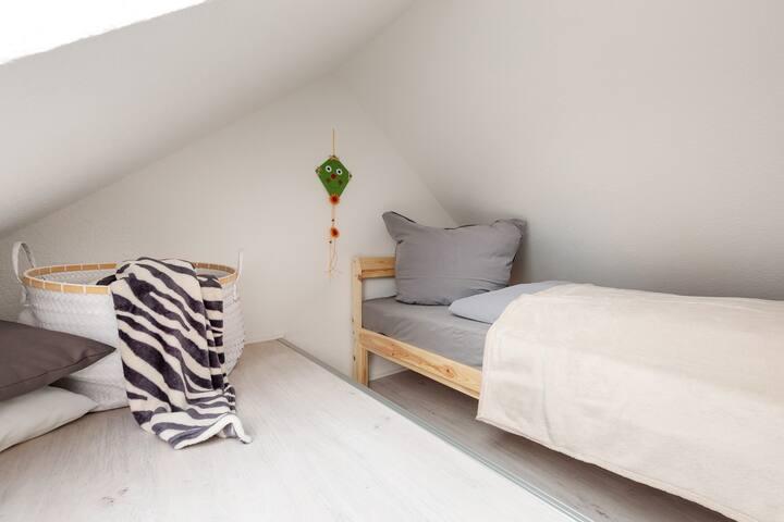 Hemsboden mit Dachfenster und Einzelbett; über eine Leiter zu erreichen