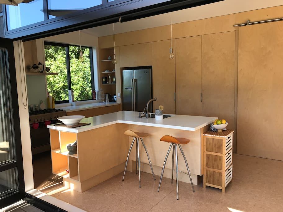 Modern fully equipped kitchen with gas hob leading onto deck with outside seating and umbrella.