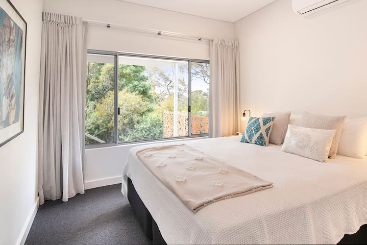 Luxurious King Bed with reverse cycle air con and ceiling fan overlooking bush.