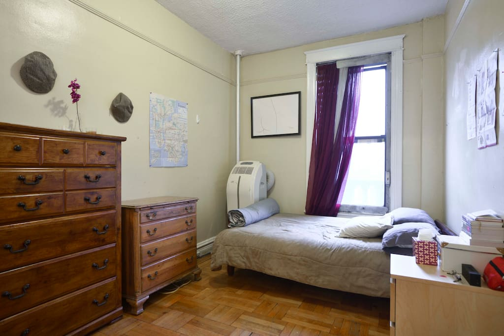 Private, well-lit bedroom. Fire escape in room, with air conditioner and large closet.