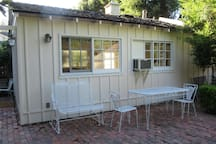 The private back patio of the cottage with bench, table and chairs for your use.