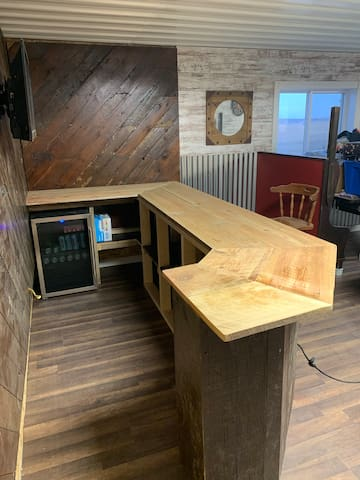 Family/Entertainment Room Bar area with 4 bar stools and bar booth for playing games on . TV on back wall for Football game viewing. With Central Air Conditioning & Heating. Dart board game, Pool table & Foosball table , TV viewing area &Outside Deck