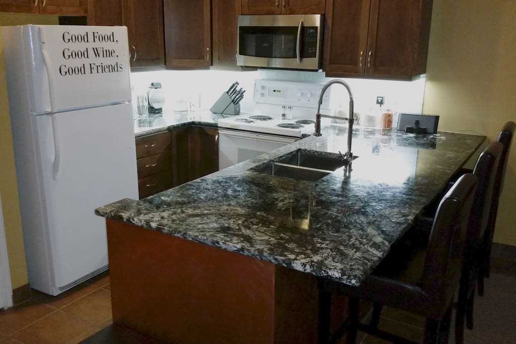 Massive granite counter-top in well lit kitchen.  High end cooking equipment so you will feel right at home.