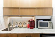 Efficiency kitchen includes Keurig, microwave, and refrigerator.