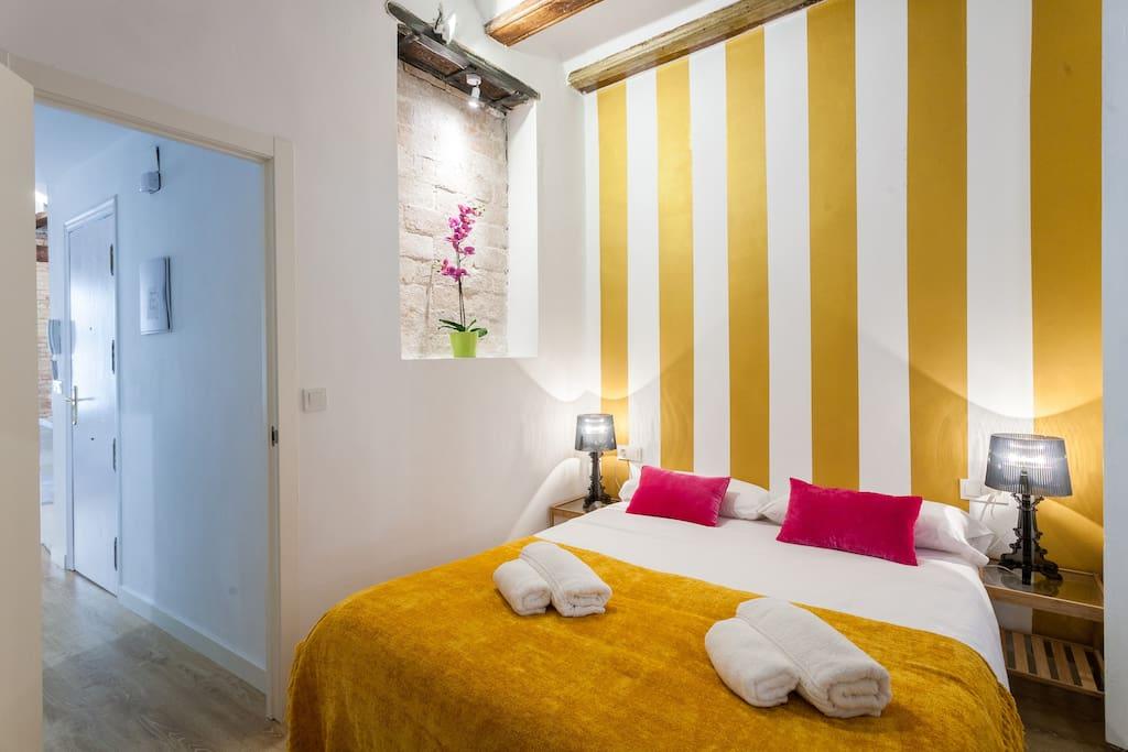 Dormitorio con vigas , Balcon y ventana pintado con rayas de Oro