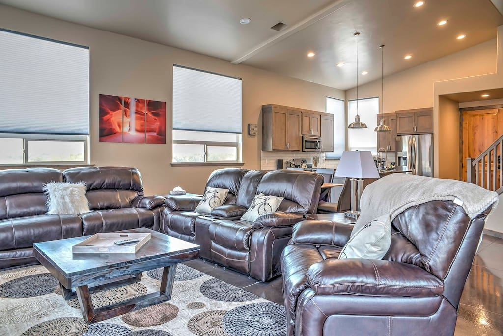 Kick back on the plush leather couches in the living room filled with natural light from the large windows framing the landscape outside.