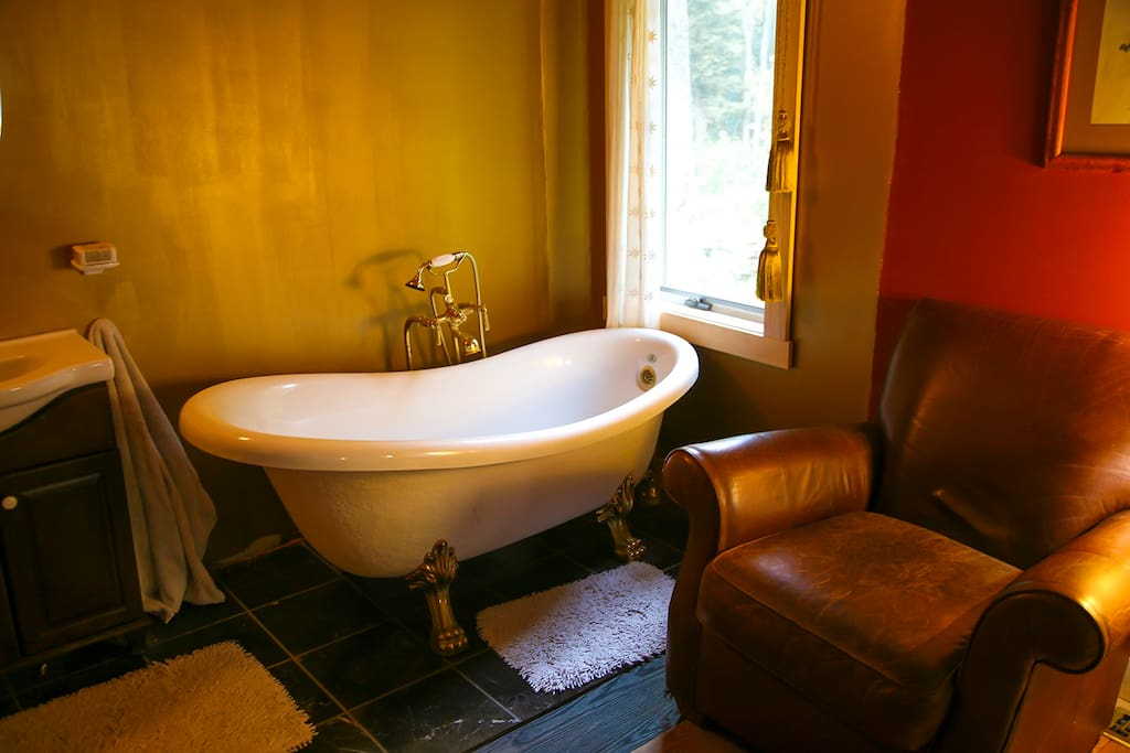 spa quality, bronze claw foot tub with overstuffed leather chair beside. relax.