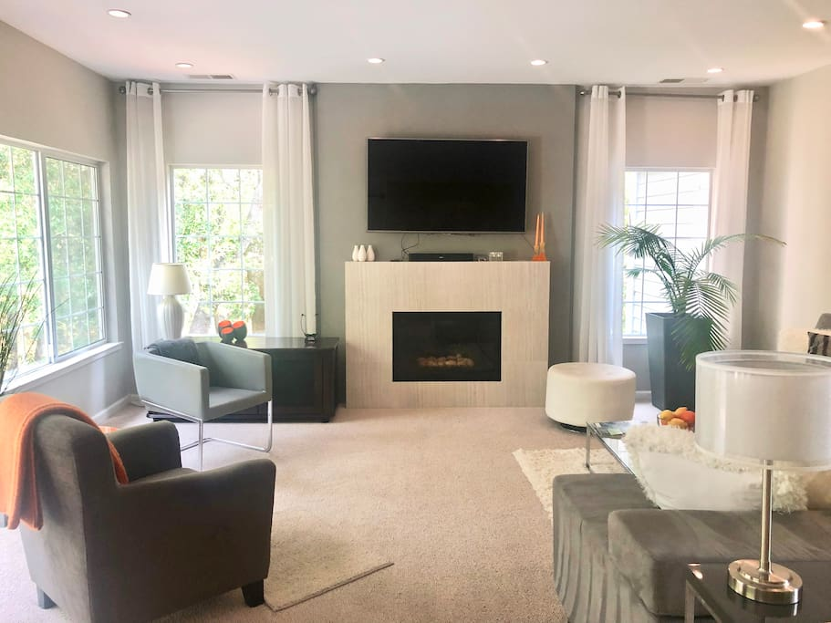 Family room with gas fireplace, smart TV, and private green views