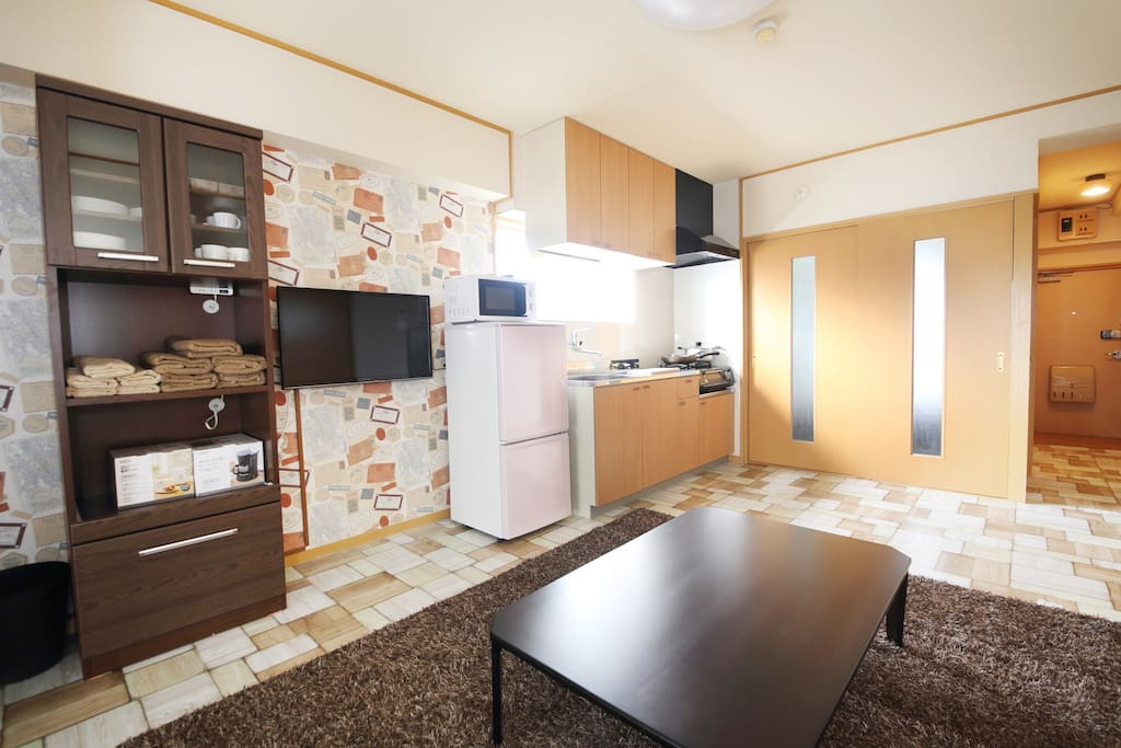 The living room and kitchen with fridge, microwave and cooking ware. キッチンとリビング。電子レンジ、冷蔵庫、食器なんでも揃っています。