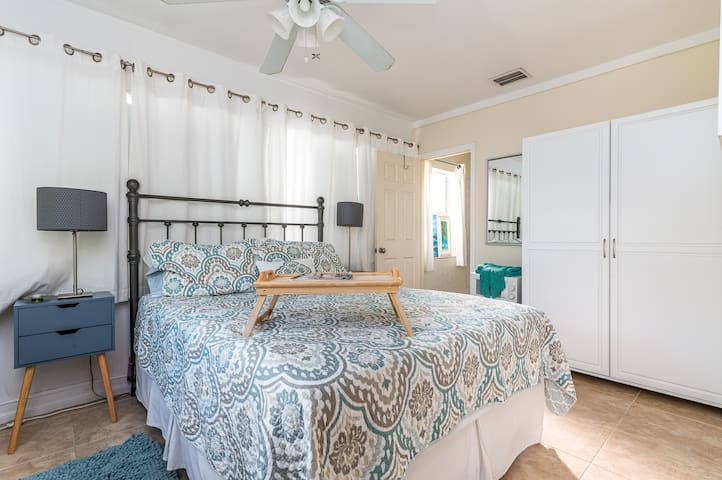 Bedroom with Queen bed and private bathroom and exit.