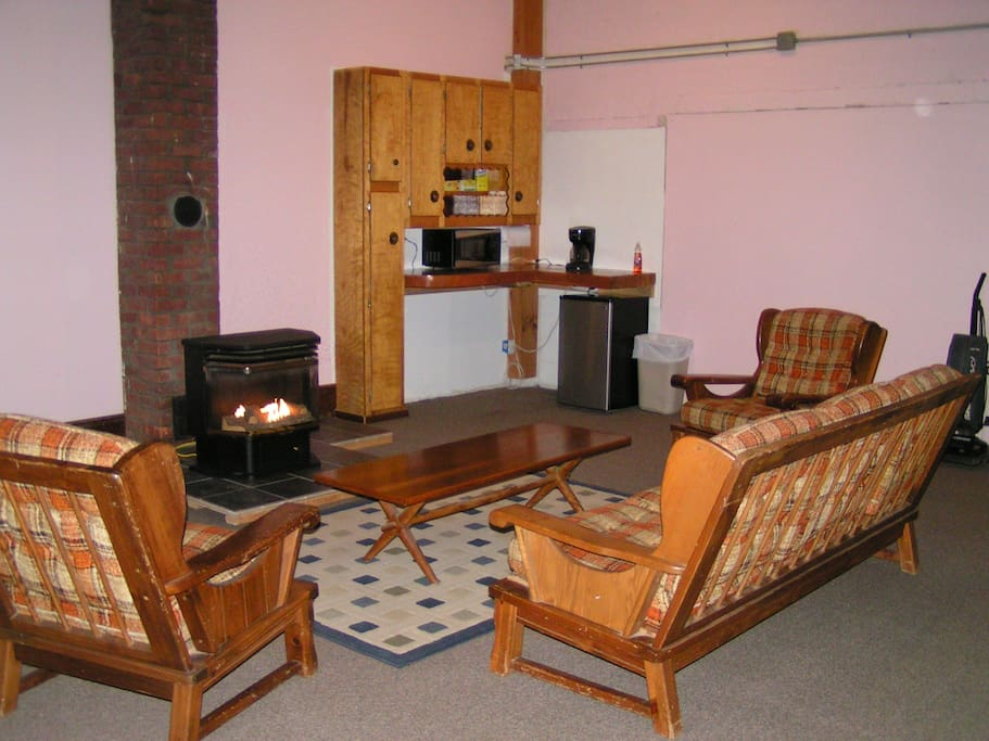 View of sitting area with fireplace and kitchenette with microwave, coffee maker, and frig.