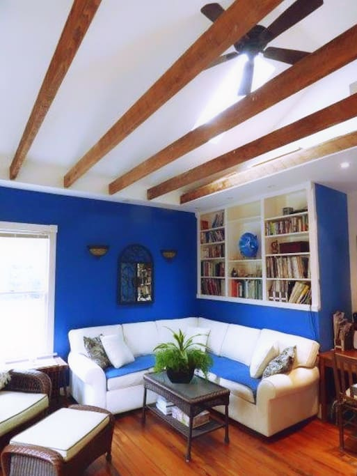 Bright blue walls, sunlight, and natural beams give this apartment a Greek island vibe.