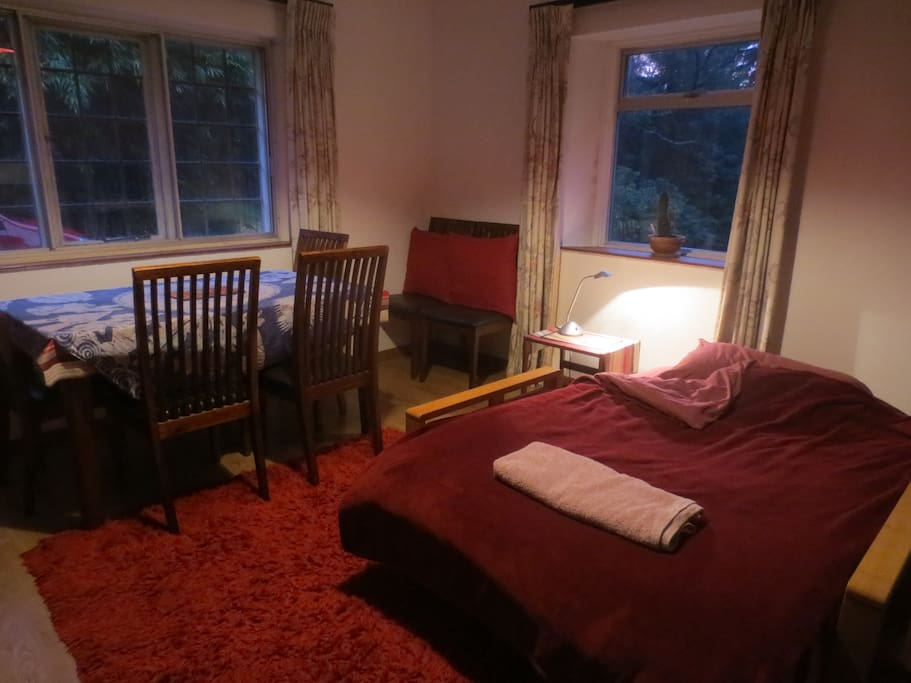 Spacious double room with futon bed and dining table. Room looks out onto an enclosed garden.