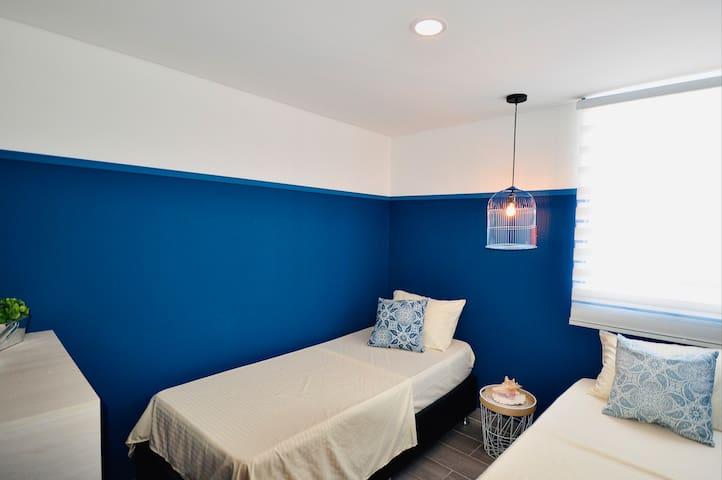 Habitación con dos camas sencillas, iluminada y aire acondicionado.