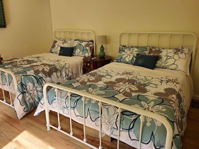 bedroom with two full beds, dresser, window, ceiling fan