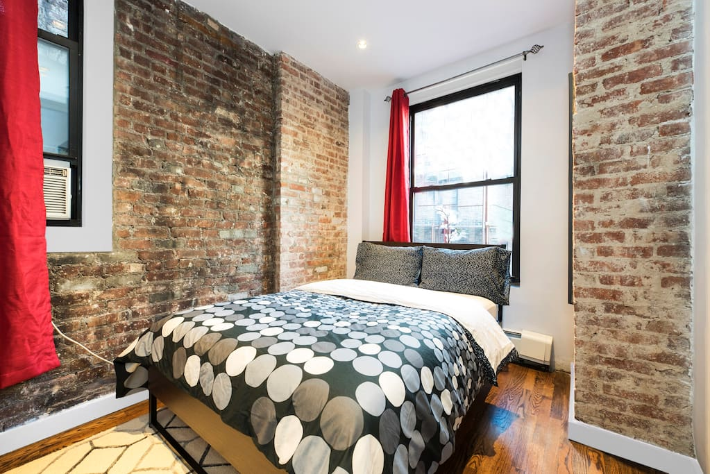 A marvelous 2nd master bedroom has two windows and exquisite exposed brick accents. A full sized double bed with new mattress & bedding. In true NYC flavor this room is seprate from the others and features curtains and a large closet for your things. Artwork & modern accents throughout.