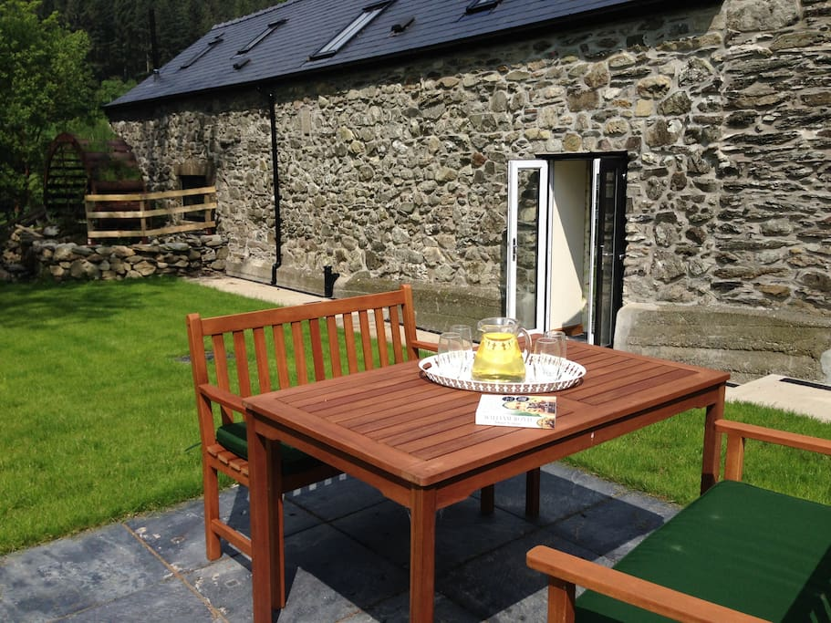 A private enclosed south facing garden with waterwheel and outdoor furniture.