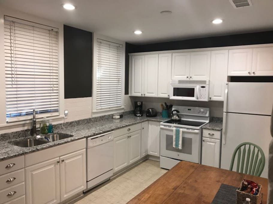 Fully furnished kitchen with granite countertops, cookware, and serving dishes.