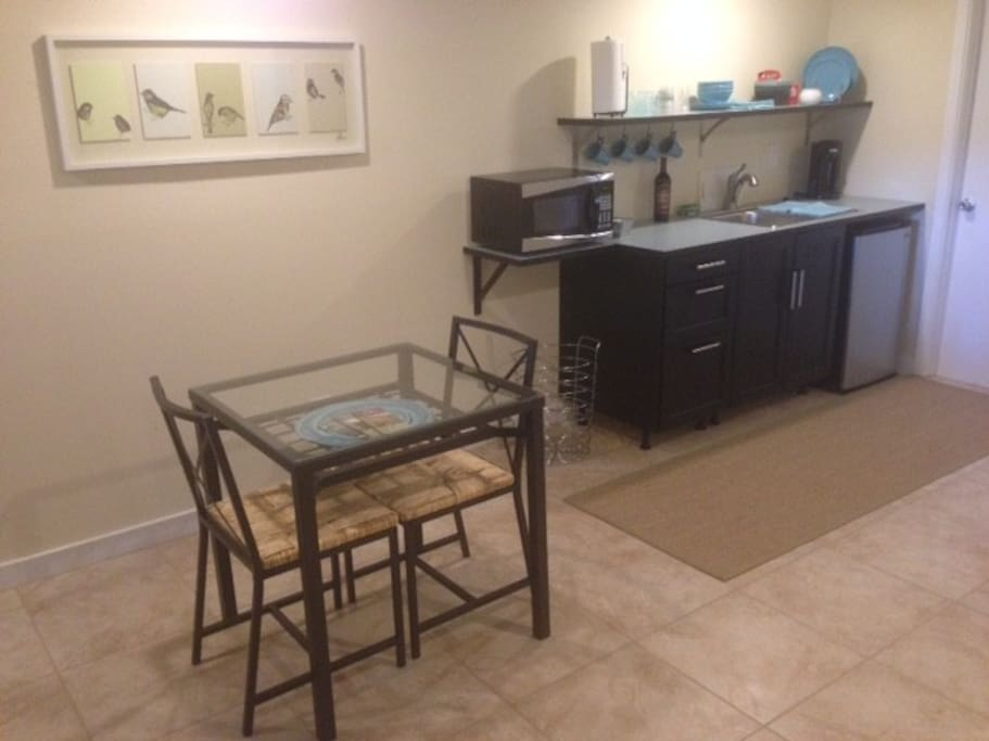 Kitchenette with microwave and fridge, dining for two.